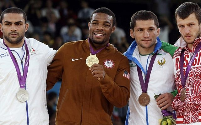 Silver medalist Sadegh Saeed Goudarzi, from Iran; gold medalist Jordan Ernest Burroughs, from the US; bronze medalist Soslan Tigiev, from Uzbekistan; and bronze medalist Denis Tsargush, from Russia, participate in the medals ceremony for men's 74-kg freestyle wrestling competition at the 2012 Summer Olympics, in London, Friday, August 10, 2012. (photo credit: AP/Paul Sancya, File)