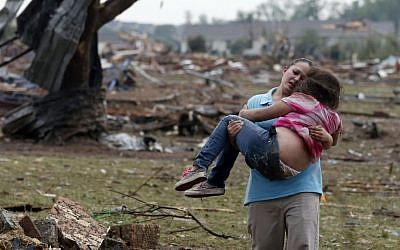 A woman carries a child through a field near the collapsed Plaza Towers Elementary School in Moore, Okla., Monday, May 20, 2013. (photo credit: AP/Sue Ogrocki)