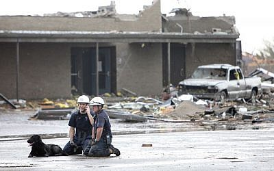 Searchers rest from operations after the tornado in Moore, Oaklahoma, on, Monday, May 20, 2013. (photo credit: AP Photo/The Oklahoman, David McDaniel)