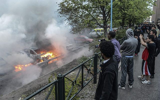 Bystanders watch a row of burning cars in the Stockholm suburb of Rinkeby after youths rioted in several different suburbs around Stockholm for a fourth consecutive night, late Thursday May 23. (Photo credit: AP Photo/Scanpix, Fredrik Sandberg)