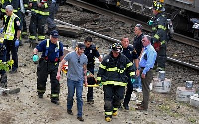 Injured passengers are transported from the scene where two Metro North commuter trains collided, Friday, May 17, 2013 near Fairfield, Conn. (Photo credit: AP/The Connecticut Post, Christian Abraham)