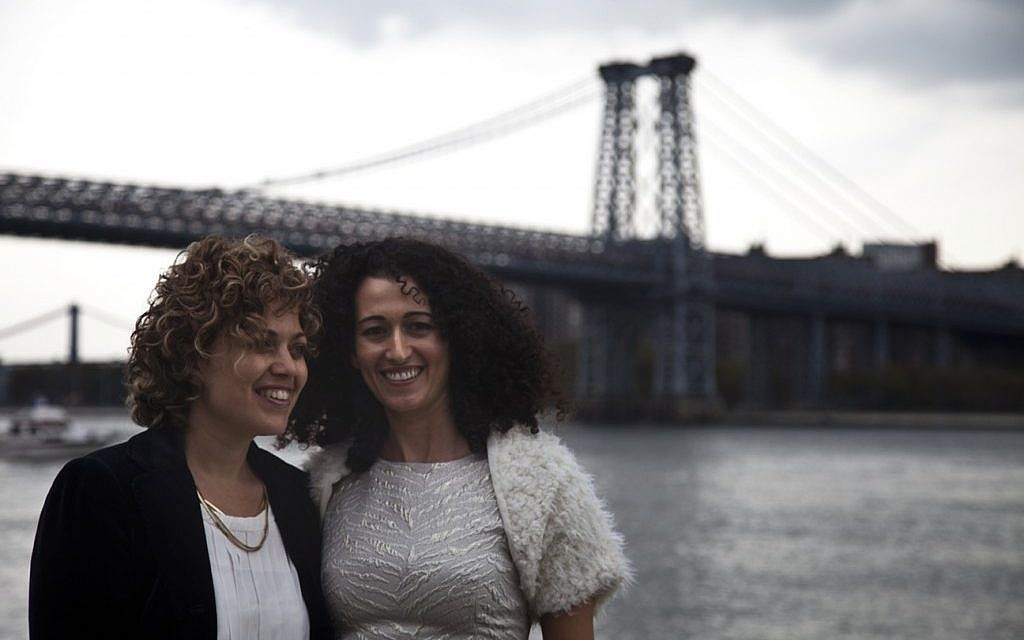 Tzila Levy, left, and Adi Lavy, married on New York City's Williamsburg Bridge, seen in the background, Oct. 27, 2012. (photo credit: Courtesy Immigration Equality/JTA)
