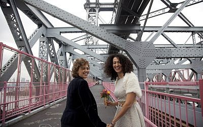 Tzila Levy, left, and Adi Lavy, standing on the Williamsburg Bridge in New York City, where they were married, Oct. 27, 2012. (photo credit: Courtesy Immigration Equality/JTA)
