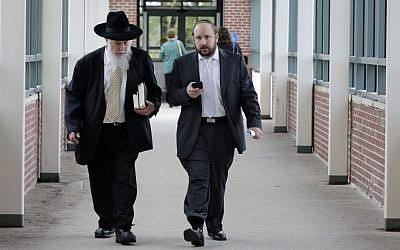 Yosef Kolko, right, walks with an unidentified man, near the Ocean County Courthouse in Toms River, NJ, Thursday, May 9, 2013, during a break in his trial on sexual assault charges. (photo credit: AP Photo/Mel Evans)