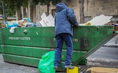 A man searches the trash in a garbage container in the center of Jerusalem. (illustrative photo by Nati Shohat/Flash90)