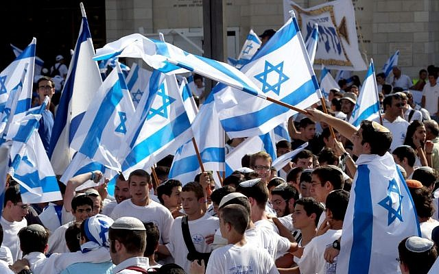 Thousands of Jewish Israelis wave Israeli flags, celebrating Jerusalem Day by walking the streets of Jerusalem, through Damascus Gate on their way to the Western Wall, on May 8, 2013. (photo by Nati Shohat/Flash90)