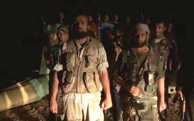Syrian rebels stand before what they claim is a downed regime helicopter. (photo credit: image capture YouTube/Syrian Observatory for Human Rights)