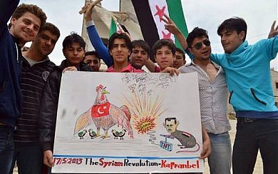 Anti-Syrian regime protesters holding a placard with a caricature of Syrian President Bashar Assad during a demonstration in Kafr Nabil, in Idlib province, northern Syria, Friday, May 17, 2013.(photo credit: AP Photo/Edlib News Network ENN)