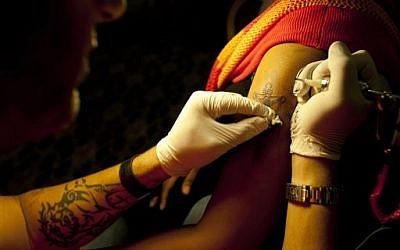 Wassim Razzouk tattoos an Ethiopian Christian Orthodox pilgrim in a hotel in Jerusalem, Monday, May 13, 2013. (photo credit: AP/Dusan Vranic)