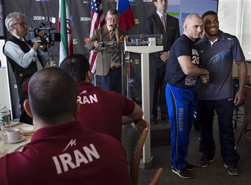 Saba Khubezhyty, second from right, of Russia shakes hands with USA's Jordan Burroughs of Lincoln, Neb., right, after their 74 kilogram class weigh-in during a news conference at UN headquarters (photo credit: AP Photo/Craig Ruttle)