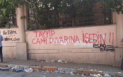 'Tayyip peed on the wall of the mosque,' reads graffiti spray-painted in red on a fence in Istanbul. Underneath the graffiti lies another, smaller inscription (in black) -- 'Assad=Erdogan.' To the left, a third inscription reads 'No Dictatorship.' (photo credit: Facebook)