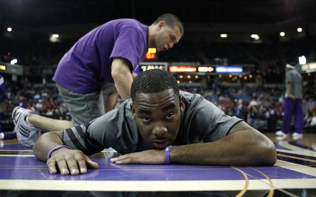 Sacramento Kings guard Marcus Thornton is seen getting stretched out from Kings strength and conditioning coach Daniel Shapiro before their NBA basketball game against the Orlando Magic in Sacramento, Calif, Jan. 8, 2012. (photo credit: AP Photo/Rich Pedroncelli)