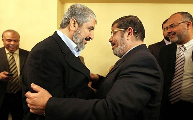 Hamas leader Khaled Mashal, left, congratulates Mohammed Morsi, the Muslim Brotherhood party's leader for winning the biggest number of seats in parliamentary elections in Cairo, January 21, 2012 (photo credit: AP)