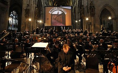An image of the Terezin concentration camp entrance in German-occupied Czechoslovakia, with a sign reading 'Arbeit Macht Frei,' is projected on a screen during a performance of Giuseppe Verdi's Requiem Mass at St. Vitus Cathedral in Prague, Czech Republic on Thursday, June 6, 2013. (photo credit: AP Photo/CTK, Stanislav Zbynek)