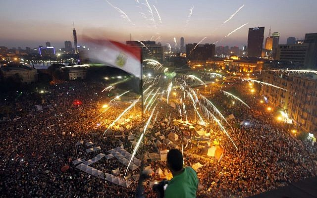 An Egyptian protester waves a national flag as Egyptians gather in Tahrir Square during a demonstration against President Mohammed Morsi in Cairo, Sunday, June 30, 2013. (photo credit: AP/Amr Nabil)