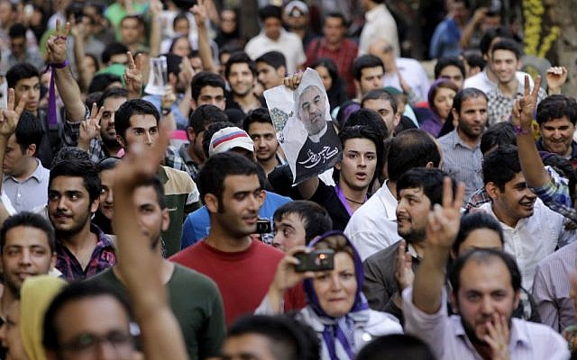 Supporters of Iranian presidential winner Hasan Rowhani, shown in poster at center, attend a celebration gathering in Tehran, Iran, Saturday, June 15, 2013. (Photo credit: AP/Vahid Salemi)