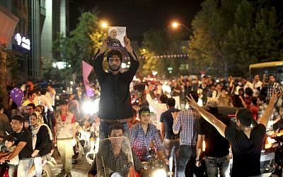 A supporter of Hasan Rowhani holds up his poster while celebrating Rowhani's victory in Tehran on Saturday. (photo credit: AP/Ebrahim Noroozi)