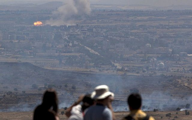 Israelis and tourists look at a fire, caused by fighting in Syria, from an observation point on Mt. Bental in the Golan Heights, near the border between the Golan Heights and Syria, Friday, June 7, 2013. (photo credit: AP/Sebastian Scheiner)