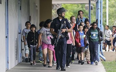 A Santa Monica police officer leads children on a field trip from Citizens of the World Charter School in Los Angeles out of Santa Monica College, where they had gone for a planetarium show, following a shooting in the area in Santa Monica, California on Friday. (photo credit: AP Photo/Reed Saxon)