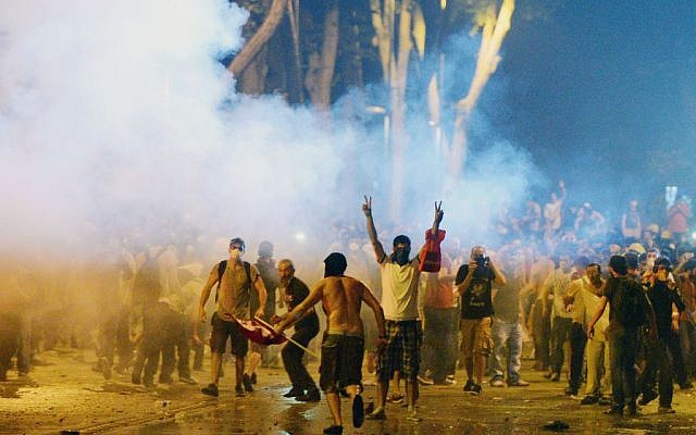 Turkish protesters clash with riot police near the former Ottoman palace, Dolmabahce, where Turkey's Prime Minister Recep Tayyip Erdogan maintains an office in Istanbul, Turkey, on June 1, 2013. (photo credit: AP)