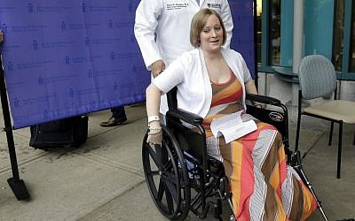 Boston Marathon bombing survivor Erika Brannock, 29, a Baltimore area pre-school teacher who lost a leg, wheels away from a news conference as she is released from Beth Israel Deaconess Medical Center in Boston, Monday, June 3, 2013. (photo credit: AP Photo/Elise Amendola)