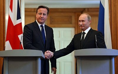 British Prime Minister David Cameron (l) shakes hands with Russian President Vladimir Putin, during a press conference in London on Sunday June 16, 2013. (photo credit: Anthony Devlin, PA Wire/AP)