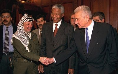 Israeli president Ezer Weizman shakes hands with Palestinian leader Yasser Arafat in Johannesburg, while South African president Nelson Mandela looks on, May 9, 1994. (photo credit: Yaacov Sa'ar/GPO)