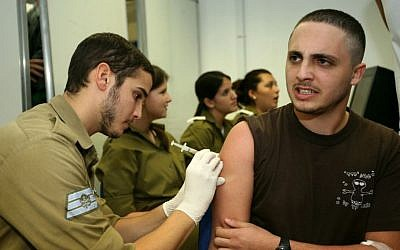 An Israeli recruit on his first day of military service gets a vaccine injection (photo credit: Moshe Shai/Flash90)