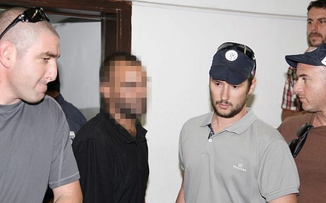 A suspect related to the 2009 Bar Noar shooting attack is escorted by police as he arrives in court in Tel Aviv, on Thursday. (photo credit: Flash90)