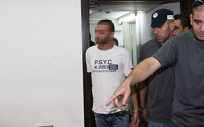A suspect related to the 2009 Bar Noar shooting attack is escorted by police as he arrives in court in Tel Aviv, on Thursday (photo credit: Flash90)