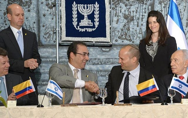 From R to L: Israeli President Shimon Peres, Israel's Economy and Trade Minister Naftali Bennett, Colombia's Industry and Tourism Minister Sergio Diaz-Granados and Colombian President Juan Manuel Santos sign a free trade agreement between Israel and Colombia during their meeting at Peres' office, in Jerusalem on June 10, 2013. (photo credit: Mark Neyman/GPO/Flash90)