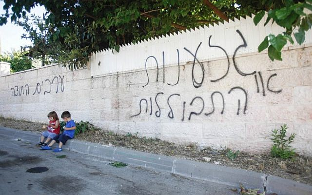 "Children sit next to a wall in the Arab-Israeli village of Abu Ghosh on June 18, 2013 where anti-Arab graffiti was sprayed overnight. The graffiti reads ""racism or assimilation"" and ""Arabs out."" (photo credit: Flash90)."