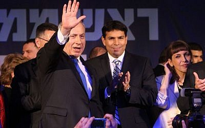 Prime Minister Benjamin Netanyahu waves to supporters after the exit polls in the general elections were announced, January 22, 2013. Standing to his left, applauding, is Likud MK Danny Danon. (Photo credit: Miriam Alster/Flash90)