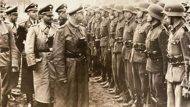 The June 3, 1944 photo provided by the US Holocaust Memorial Museum shows Heinrich Himmler, centre, SS Reichsfuehrer-SS, head of the Gestapo and the Waffen-SS, and Minister of the Interior of Nazi Germany from 1943 to 1945, as he reviews troops of the Galician SS-Volunteer Infantry Division. Michael Karkoc a top commander whose Nazi SS-led unit is blamed for burning villages filled with women and children lied to American immigration officials to get into the United States and has been living in Minnesota since shortly after World War II, according to evidence uncovered by The Associated Press. (photo credit: AP/ US Holocaust Memorial Museum, courtesy of Atlantic Foto Verlag Berlin)