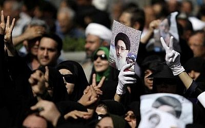 Mourners show the Victory sign during a funeral ceremony for Ayatollah Jalaluddin Taheri (pictured in poster), in Isfahan, Iran, on June 4, 2013. (photo credit: AP/Fars News Agency, Hamid Reza Nikoumaram, File)
