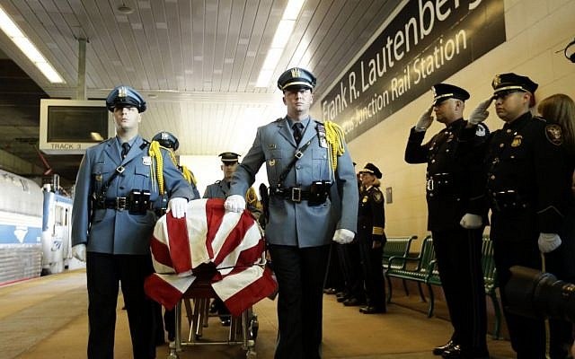 The casket of US Sen. Frank Lautenberg is transferred to an Amtrak train en route to Washington D.C. during a Color Guard ceremony at the Frank R. Lautenberg Rail Station on Wednesday in Secaucus, N.J. (photo credit: AP/Frank Franklin II)