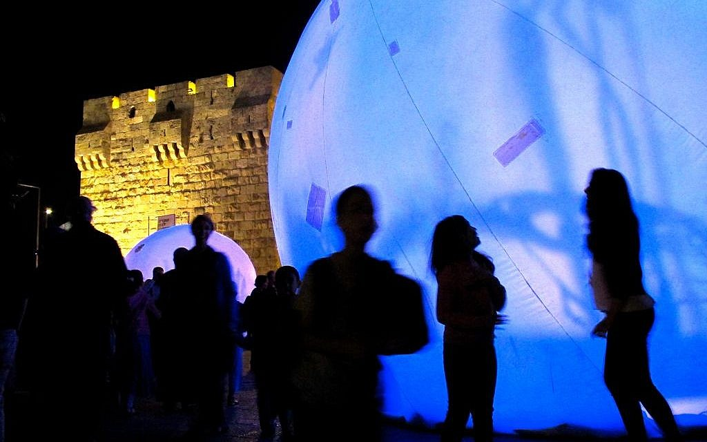Spectators gaze at 'Spirit Light of the Forest,' created in Montreal by Lucion Media. Located in front of Jaffa Gate, seven huge bubbles come together to form a mosaic of light and shadow (photo credit: Leeor Bronis/Times of Israel)