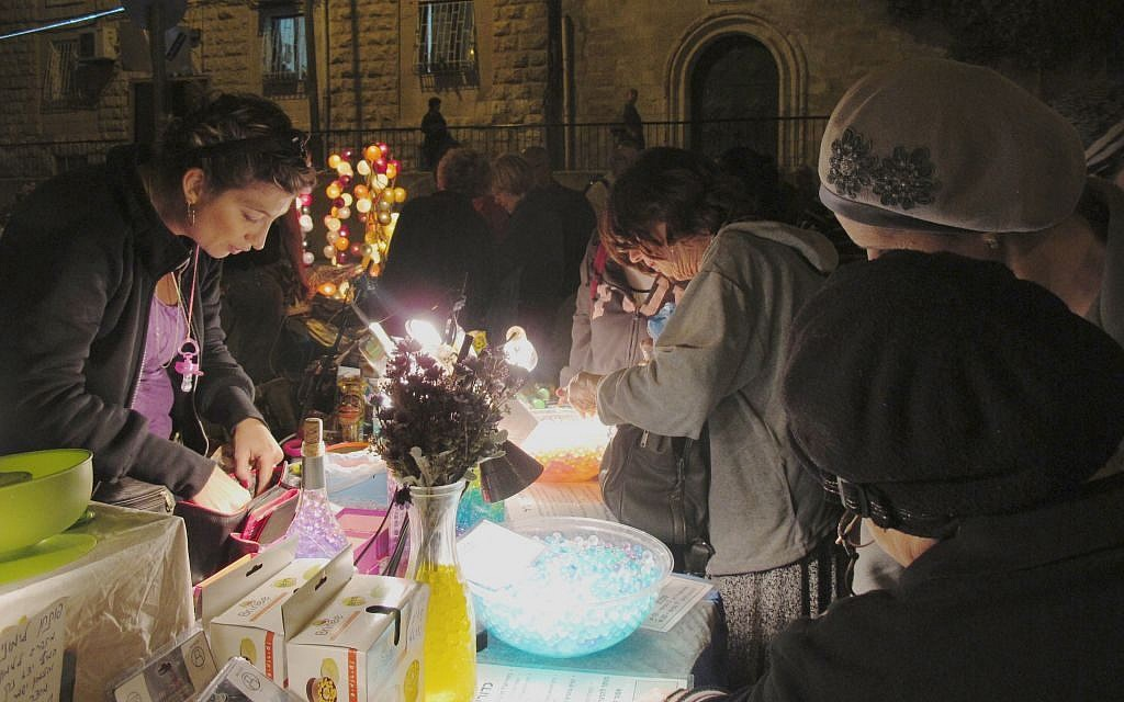 Local merchants take the opportunity to engage with light show participants, selling beads, lamps and other shiny, light-related objects (photo credit: Leeor Bronis/Times of Israel)