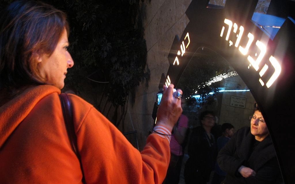 """Part of the """"Light in the Shadow"""" exhibit by artist Dan Groover, guests can read inscriptions carved on multiple mirrors and light fixtures (photo credit: Leeor Bronis/Times of Israel)"""