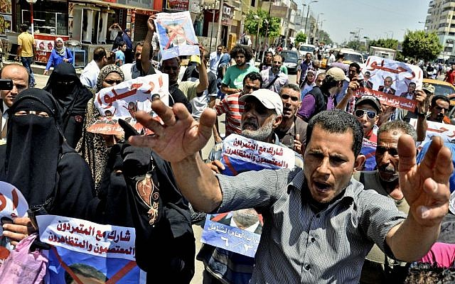 Protesters chant slogans against Egyptian President Mohammed Morsi outside a court in Ismailia, Egypt. (photo credit: AP/Mostafa Darwish, File)