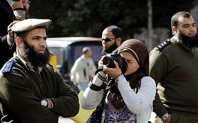 A journalist photographs Egyptian Salafi Muslims, unseen, during a protest in support of bearded police officers who were prevented from carrying out their work in the interior ministry, in front of the Shura Council, the upper house of Parliament, in Cairo, Egypt. (photo credit: AP/Amr Nabil)