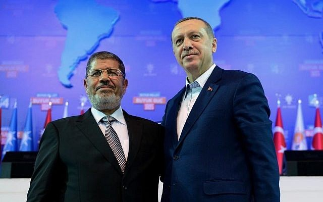 Turkey's Prime Minister Recep Tayyip Erdogan, right, and Egypt's former president Mohammed Morsi salute the members of Turkey's ruling Justice and Development Party in Ankara, Turkey in Sept. 2012 (photo credit: AP/Kayhan Ozer)