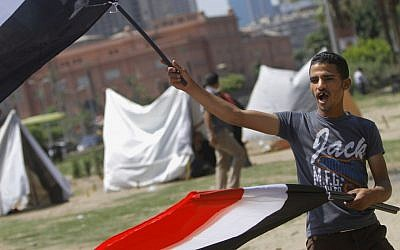 An Egyptian flag vendor waves flags in front of new erected strike tents in Tahrir Square, the focal point of Egyptian uprising in Cairo, Egypt, Saturday, June 22, 2013. (photo credit: AP/ Amr Nabil)
