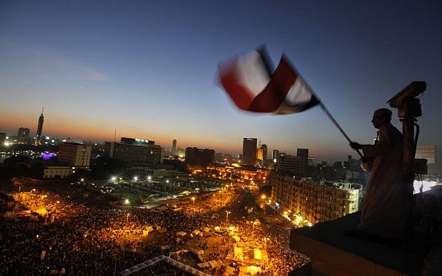 An Egyptian protester waves the national flag over Tahrir Square, the focal point of the Egyptian uprising,  June 28, 2013.  massive nationwide protests planned by the opposition this weekend demanding Mohammed Morsi's removal. (AP Photo/Amr Nabil)