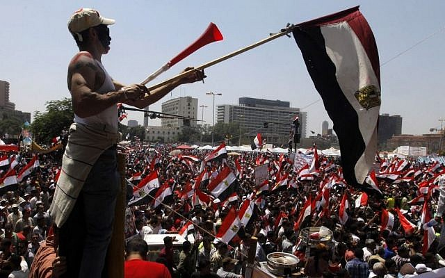 Egyptian protesters chant slogans and wave national flags in Tahrir Square, the focal point of the Egyptian uprising, in Cairo, on Sunday, June 30, 2013. (photo credit: AP/Amr Nabil)