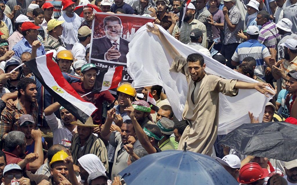 An Egyptian supporter of Egypt's Islamist President Mohammed Morsi dances by a poster of Morsi during a rally outside the Rabia el-Adawiya mosque near the presidential palace in Cairo, Saturday, June 29 (photo credit: APAmr Nabil)