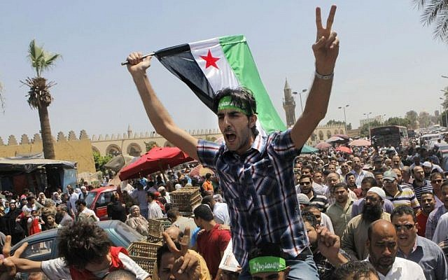 Egyptian Salafis shout slogans against Syrian President Bashar Assad as one waves a Syrian revolutionary flag during a rally after the Friday prayers at Amr Ibn Al As mosque, in Cairo, Egypt, on Friday, June 14, 2013 (photo credit: AP/Amr Nabil)