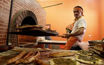 "An employee at ""Damashki"" (or ""The Guy From Damascus"") bakery co-owned by Bassel Shunar, a Palestinian by origin who was born in Syria but who fled the country and arrived in the Gaza Strip two months ago. (photo credit: AP Photo/Hatem Moussa)"