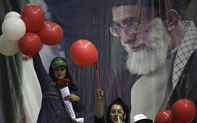 Supporters of Iranian presidential candidate Ali Akbar Velayati, a conservative former foreign minister, gather in front of a portrait of supreme leader Ayatollah Ali Khamenei during a campaign rally on Wednesday in Tehran (photo credit: AP/Vahid Salemi)