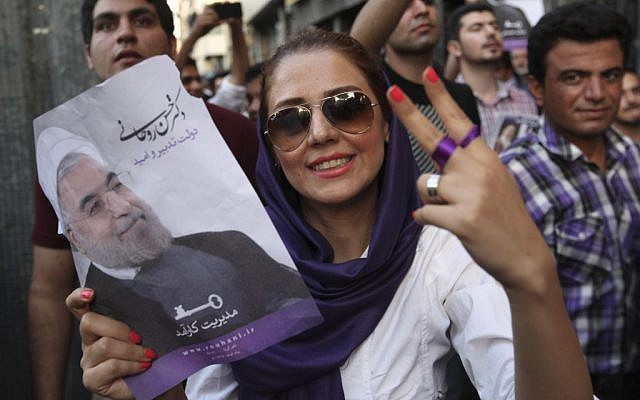 A female supporter of Iranian presidential candidate Hasan Rowhani flashes a victory sign as she holds his poster during a celebration gathering in Tehran, Iran, Saturday, June 15, 2013 (photo credit: AP)